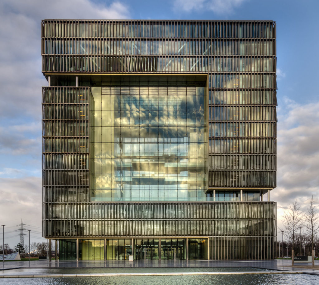Das Foto zeigt das ThyssenKrupp Hauptquartier in Essen, Westviertel. Ein großer Kubus, vor dem ein großer flacher Brunnen steht.