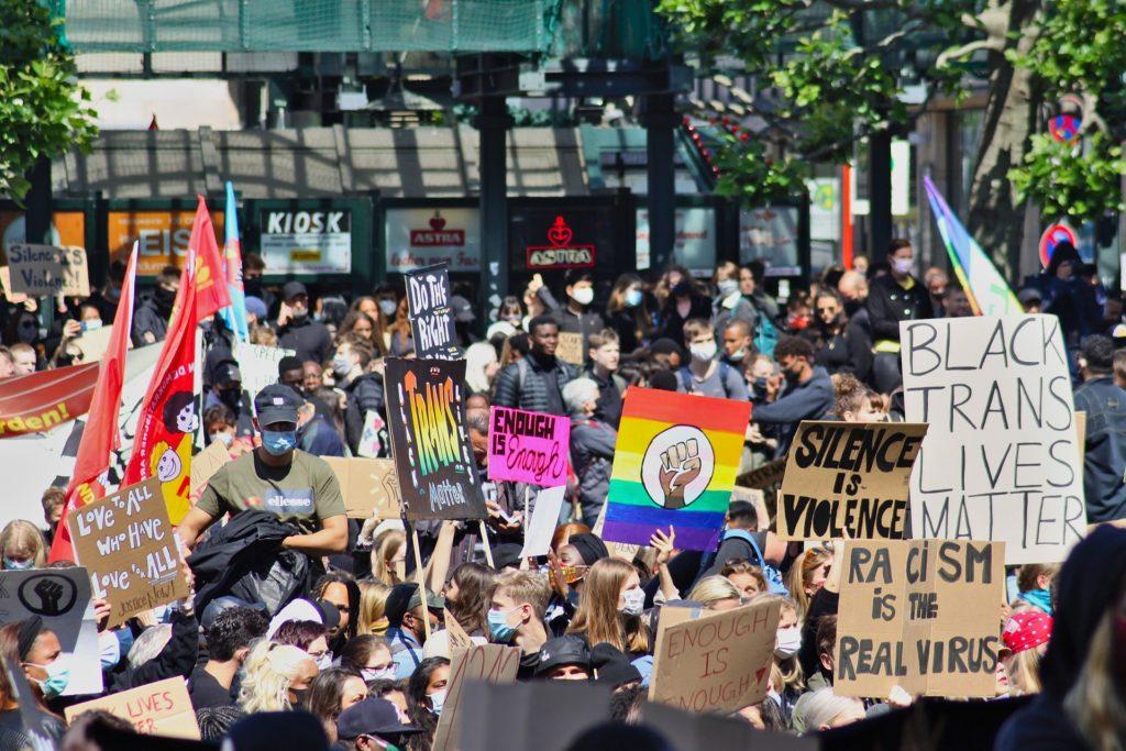 Viele Menschen mit bunten Fahnen und Schildern auf einer Demonstration gegen Rassismus